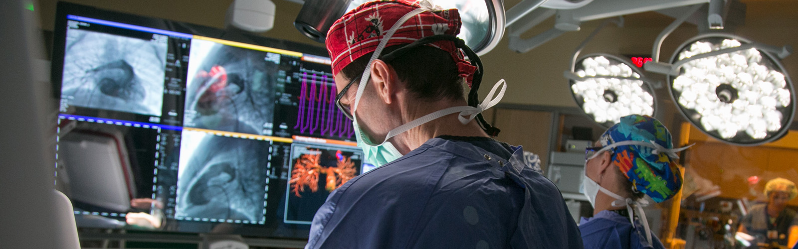 surgeon in front of a bank of monitors