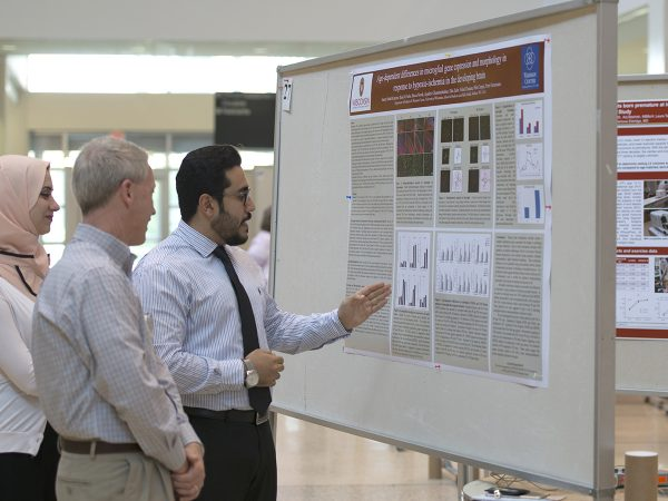 Scott Hagen, MD, (center) listens as Samer Abdul Kareem, MD, and Rand Al-Subu, MD, research assistants in the lab of Pelin Cengiz, MD, describe their research poster.