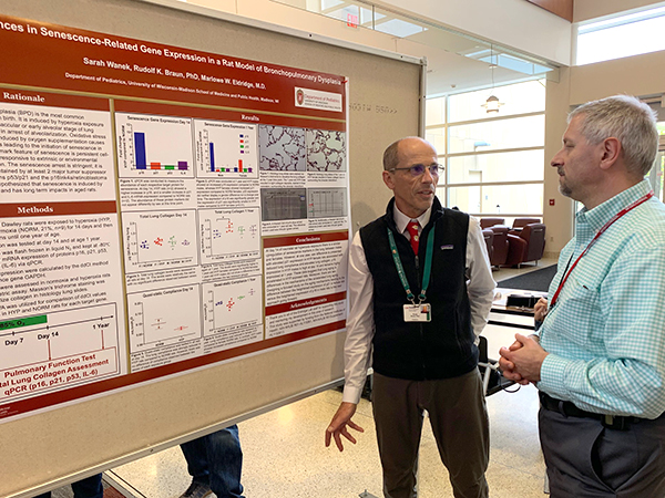 Critical Care senior scientist Rudolf Braun, PhD, discusses his poster on senescense-related gene expression in a rat model of bronchopulmonary dysplasia with Hematology, Oncology & Bone Marrow Transplant faculty member Mario Otto, MD, PhD.