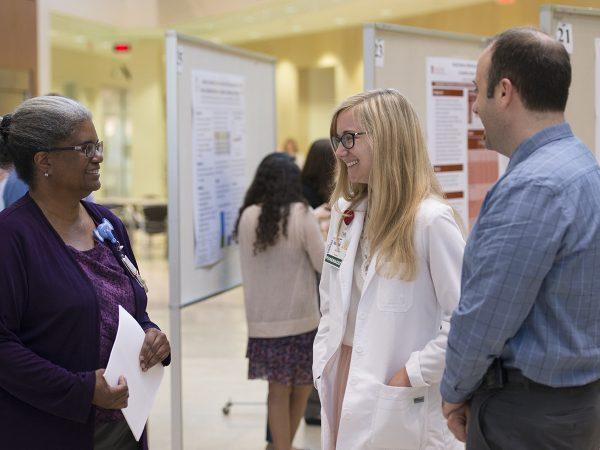 Sheryl Henderson, MD, (on left) talks with Erin McCreary, PharmD, the UW Health infectious diseases pharmacy resident, and Randy Braun, PharmD, a pharmacy clinical instructor.
