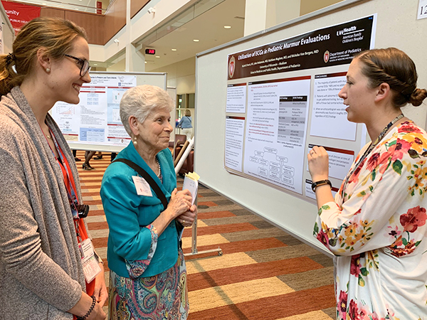 Resident Lindsay McGowan, MD (on left), listens in while resident Rachel Harris, DO (on right), discusses her poster on use of ECG in pediatric murmur evaluation with Department of Pediatrics Chair Ellen Wald, MD.