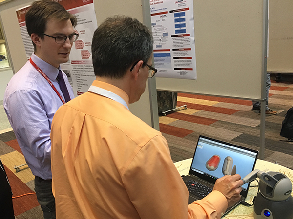 Brandon Tomlin, MD, watches as Jonathan Fliegel, MD, tries his hand at a virtual-reality–based neonatal intubation simulator