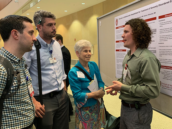 Resident Nicholas Beam, MD, and UW School of Medicine and Public Health student Patrick O'Donnell (on left) listen as resident Dane Hammer, MD (on right), discusses his poster on diuresis for adolescents hospitalized for severe eating disorders with Department of Pediatrics Chair Ellen Wald, MD.