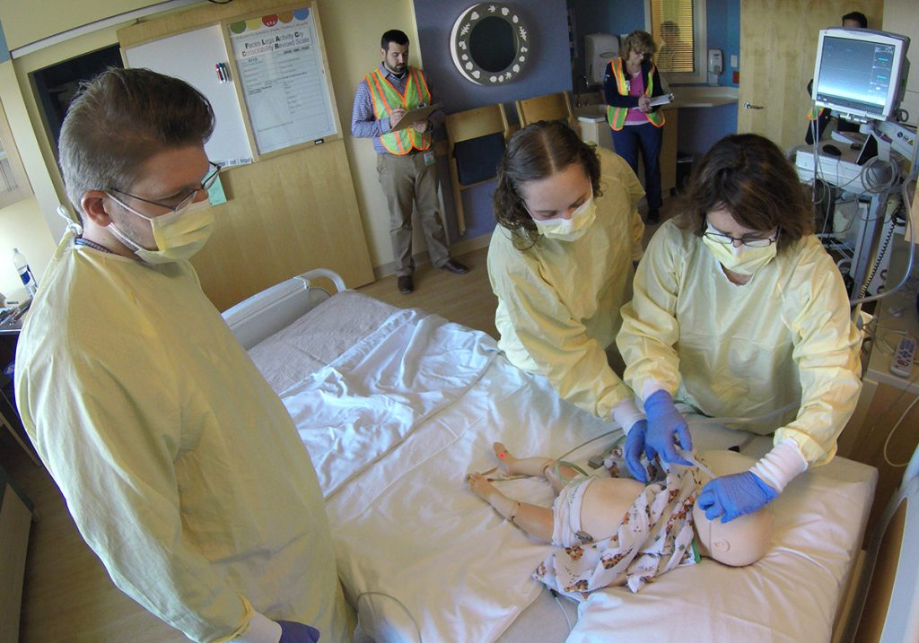 A team of nurses, respiratory therapists and residents respond to a simulated patient while the simulation team observes in the background.