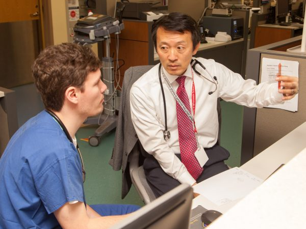 Pediatrics resident Dane Hammer, MD, talks with Michael Kim, MD, an associate professor in the Department of Pediatrics and the pediatric emergency medicine section chief in the BerbeeWalsh Department of Emergency Medicine.