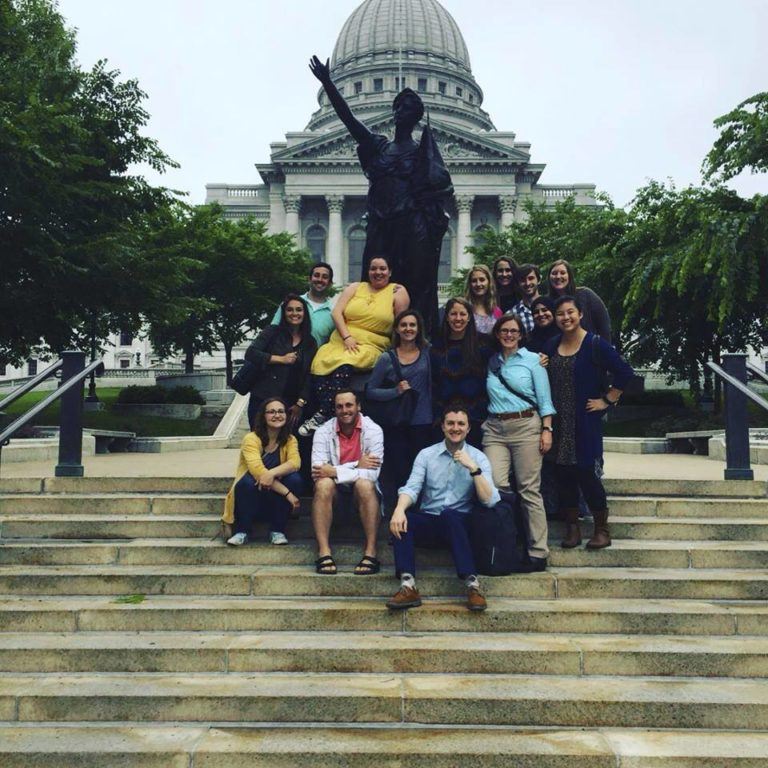Residents standing before statue in front of Capitol building