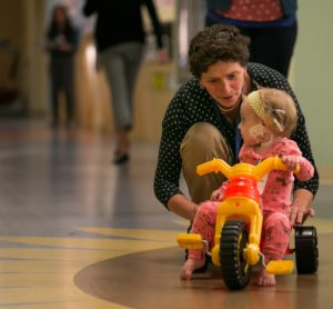 Dr. Carol Diamond playing with a child on a tricycle