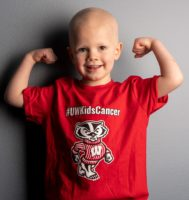 young patient flexing muscles, wearing #UWKidsCancer tshirt