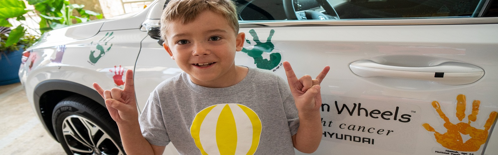 young child near Hyundai Hope on Wheels vehicle with painted handprints