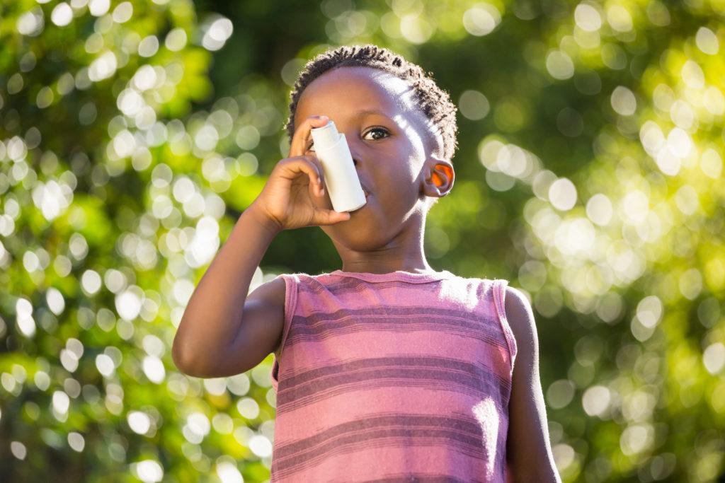 Boy using a asthma inhalator in a park