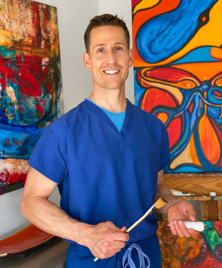 doctor holding paintbrush in front of paintings