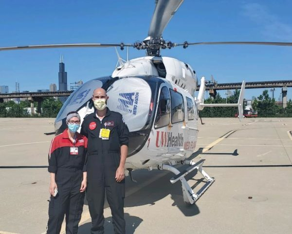 two people standing in front of helicopter