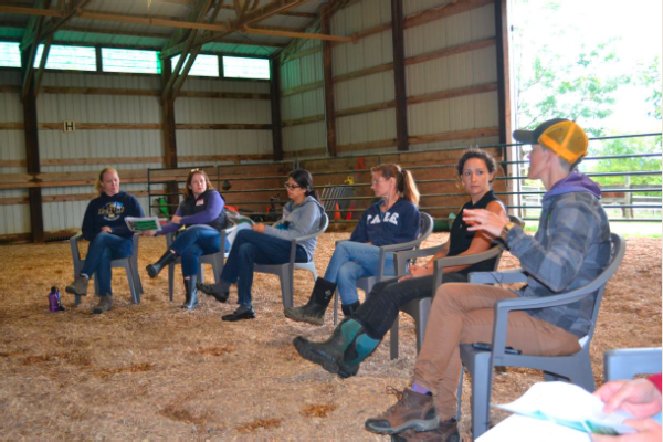 group of people sitting in a row in a barn