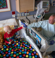 parent holding the hand of a child in a hosptial bed
